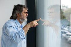 Profesor que se coloca al lado de una ventana Imagen de archivo