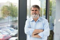 Profesor que se coloca al lado de una ventana Foto de archivo