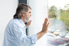 Profesor que se coloca al lado de una ventana Foto de archivo libre de regalías
