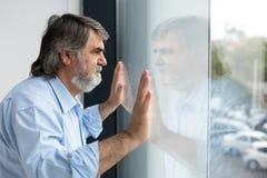 Profesor que se coloca al lado de una ventana Imagen de archivo libre de regalías