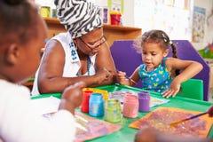 Profesor que se sienta con los niños en una clase preescolar, cierre para arriba imagenes de archivo