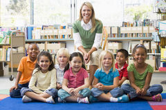 Profesor que se sienta con los niños en biblioteca Imagen de archivo libre de regalías