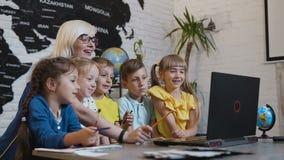 Profesor que se sienta en el escritorio al lado de estudiantes como discuten la información sobre el ordenador portátil Los alumn almacen de video