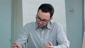 Profesor que se sienta en el escritorio en clase y charla a un estudiante Fotografía de archivo