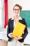 Profesor que sostiene la carpeta en escuela delante de una clase Imágenes de archivo libres de regalías