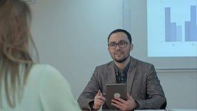 Profesor que sostiene la tableta digital en manos mientras que enseña a lecciones en sala de clase de la escuela a los estudiante Imagenes de archivo