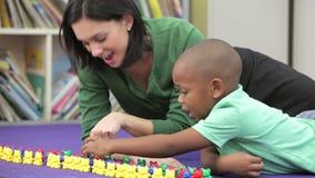 Profesor Showing Boy How a contar con los juguetes plásticos almacen de metraje de vídeo