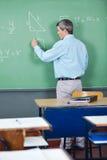 Profesor Solving Mathematics On Greenboard adentro Fotografía de archivo