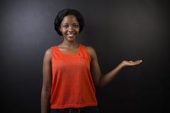 Profesor surafricano o afroamericano de la mujer en fondo del tablero del negro de la tiza Fotos de archivo libres de regalías