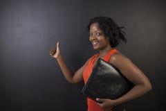 Profesor surafricano o afroamericano de la mujer en fondo del tablero del negro de la tiza Imagenes de archivo