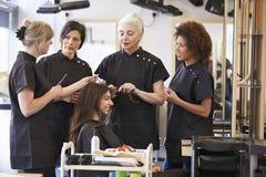 Profesor Training Mature Students en peluquería foto de archivo