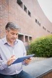 Profesor używa cyfrową pastylkę w kampusie zdjęcie royalty free