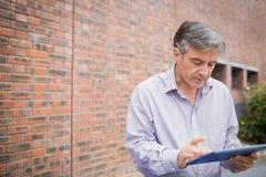 Profesor używa cyfrową pastylkę w kampusie fotografia stock