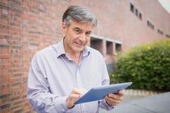 Profesor używa cyfrową pastylkę w kampusie obraz royalty free