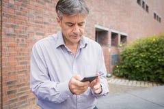 Profesor używa telefon komórkowego w kampusie obraz stock