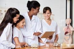 Profesor Using Digital Tablet con los estudiantes en el escritorio Imagen de archivo libre de regalías
