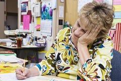 Profesor Working At Desk Imagen de archivo libre de regalías