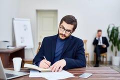 Profesor Writing Book en oficina Imágenes de archivo libres de regalías