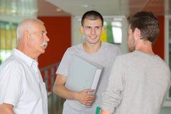 Profesor y adolescentes que hablan en el pasillo Imagen de archivo