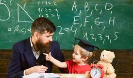 Profesor y alumno en el birrete, pizarra en fondo Concepto travieso del niño El padre con la barba, profesor enseña fotos de archivo libres de regalías