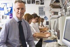Profesor y alumnos que estudian en los ordenadores imágenes de archivo libres de regalías