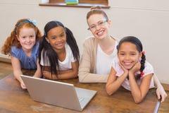 Profesor y alumnos que miran el ordenador portátil Foto de archivo libre de regalías