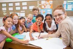 Profesor y alumnos que trabajan en el escritorio junto Imagenes de archivo