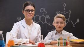 Profesor y colegial de la química de la señora joven que miran a la cámara y que sonríen, lección metrajes