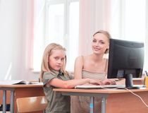 Profesor y colegiala en el ordenador Imágenes de archivo libres de regalías