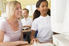 Profesor y colegiala que estudian en un ordenador Imagen de archivo libre de regalías