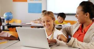 Profesor y colegiala que usa el ordenador portátil en sala de clase
