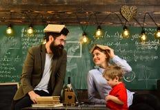 Profesor y estudiante en la sala de clase en una escuela, estudiantes adultos sonrientes de la escuela durante rotura en interior Fotografía de archivo