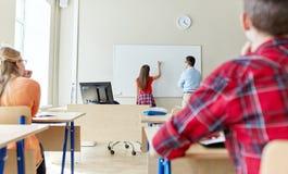 Profesor y estudiante que escriben a bordo en la escuela Imagen de archivo