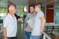 Profesor y estudiantes adolescentes que hablan en pasillo Imagen de archivo libre de regalías