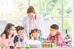 Profesor y estudiantes en el laboratorio, flotador del humo hacia fuera imagen de archivo libre de regalías