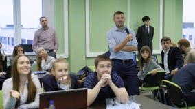 Profesor y estudiantes en la audiencia que espera el resultado de la competencia almacen de metraje de vídeo