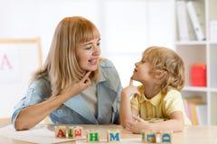 Profesor y niño pequeño de la mujer en la lección privada imagen de archivo libre de regalías
