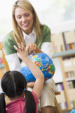 Profesor y niños de jardín de la infancia que miran el globo