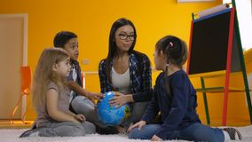 Profesor y niños que discuten el globo en guardería metrajes