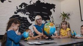 Profesor y niños que discuten el globo en sala de clase de la geografía en la escuela primaria Grupo de estudiantes caucásicos ad metrajes