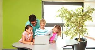 Profesor y niños usando el ordenador portátil en sala de clase almacen de metraje de vídeo