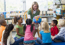 Profesor y niños que miran el globo Fotos de archivo