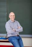Profesor Z ręka Krzyżującym obsiadaniem Na biurku zdjęcia stock