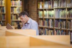 Profesora obsiadanie przy biurkiem używać jego laptop zdjęcia stock