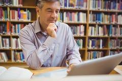 Profesora obsiadanie przy biurkiem używać laptop zdjęcie royalty free