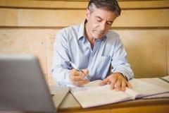 Profesora writing w książce przy biurkiem obraz royalty free