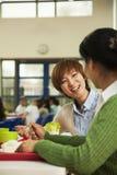 Profesores que hablan en el almuerzo en cafetería de la escuela Fotografía de archivo libre de regalías