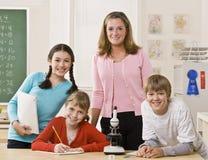 Professeur, étudiants et microscope dans la salle de classe Image stock