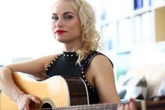 Professeur adulte blond de guitare jouant l'instrument et regardant in camera photos libres de droits