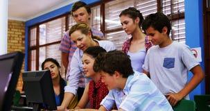 Professeur aidant des étudiants dans la classe d'ordinateur clips vidéos